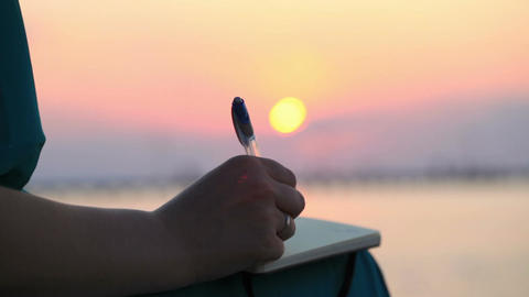 Woman writing in her diary at sunset Footage