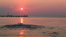 Man swimming in the sea at sunset Stock Video Footage