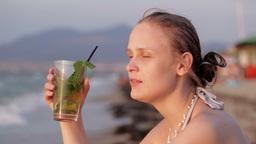 Woman enjoying an evening cocktail Stock Video Footage