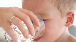 Little boy drinkng a glass of fresh water Stock Video Footage