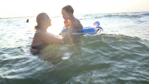 Mother bathing in the beach with her young child Stock Video Footage
