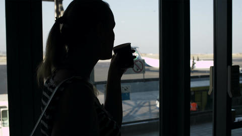 Young woman drinking coffee at the airport Stock Video Footage