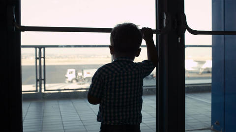 Young boy looking through window in the airport Footage