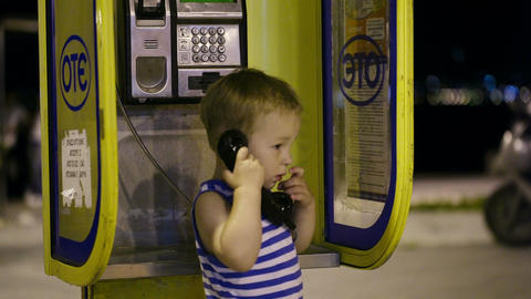 Young boy talking to the phone in a booth Stock Video Footage