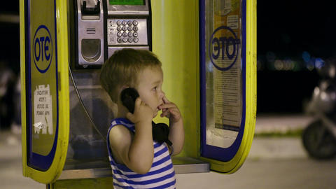 Young boy talking to the phone in a booth Footage