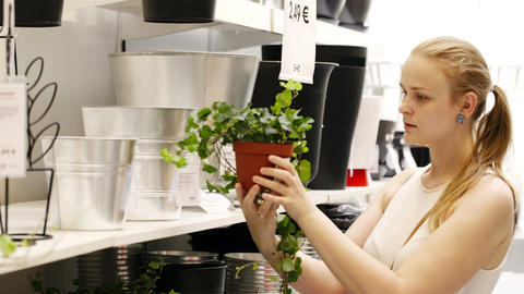 Young blond woman looking at vases with plants in Stock Video Footage