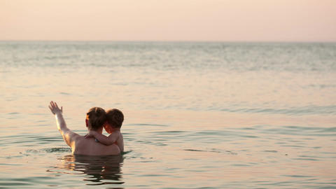 Loving mother and her child bathing in the sea Stock Video Footage