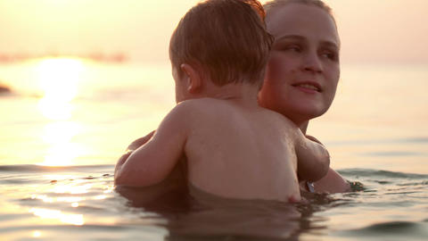 Son and mother embracing in the sea Stock Video Footage