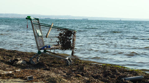 Abandoned shopping trolley on the beach Stock Video Footage