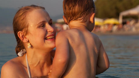 Happy mother tossing up her son in the sea Stock Video Footage