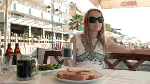 Young woman having a meal in an outdoor restaurant Stock Video Footage