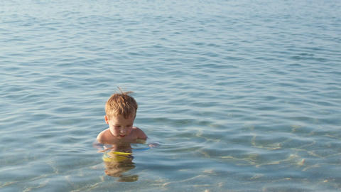 Little Boy Playing In The Shallow Sea stock footage