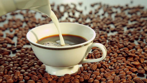 Pouring milk in a white cup with coffee Footage