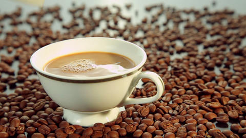 Pouring milk in a white cup with coffee Stock Video Footage