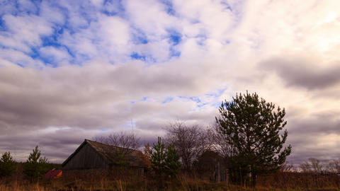 Clouds sweep over the barn. Time Lapse. 4K Footage
