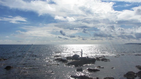 fisherman with spinning near sea in sunlight - tim Stock Video Footage