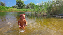 little girl playing in the river Footage