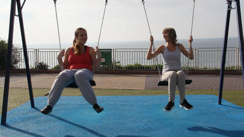 Two Girls Swinging On A Swing stock footage