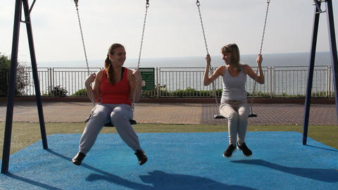 two girls swinging on a swing Stock Video Footage