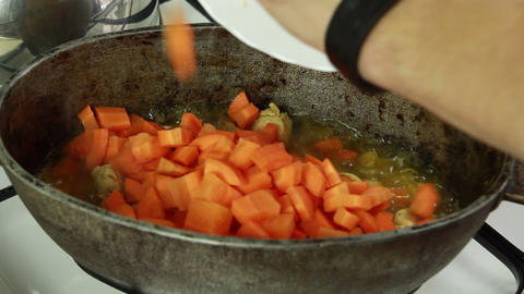 Chief adding sliced carrot and mixing with meat in Stock Video Footage
