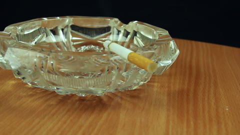 Smoking cigarette in ashtray dolly shot back view Stock Video Footage