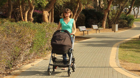 mother walking with a baby in a stroller Stock Video Footage