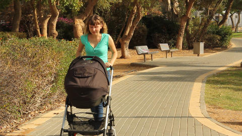 mother walking with a baby in a stroller Footage