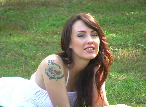 Beautiful Brunette Lying in the Grass (2) Stock Video Footage