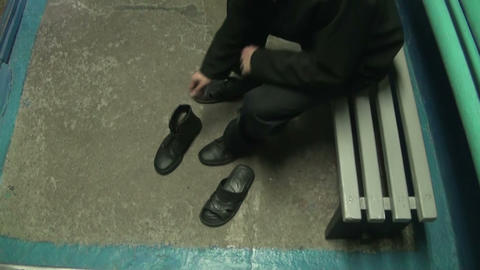 Jailed a man puts shoes Stock Video Footage