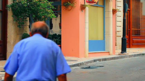 A man walking down the street of a small town Stock Video Footage