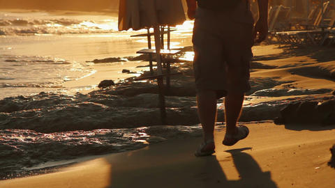 man walking along the beach at sunset Stock Video Footage