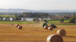 Tractor passing in a meadow with scattered hay bal Stock Video Footage