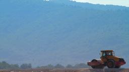 Compactor flattening road in rural area Footage