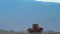 Compactor flattening road in rural area Stock Video Footage