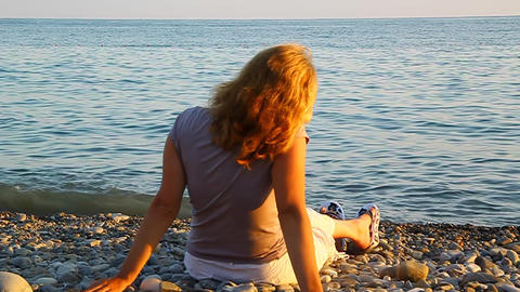 A Woman Sitting On The Beach By The Sea And Admiri stock footage