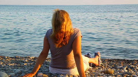 A woman sitting on the beach by the sea and admiri Stock Video Footage