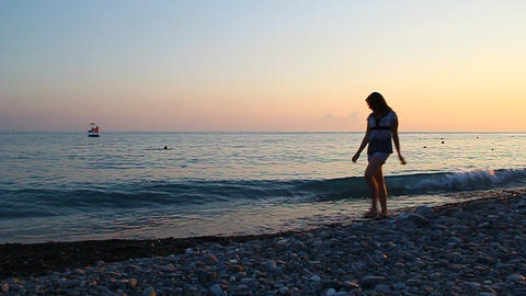 Young beautiful girl walking on the beach at sunse Footage