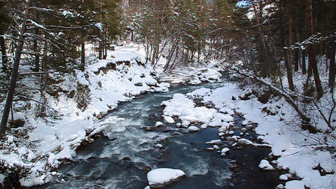 Pure blue mountain river flowing among the snow-co Stock Video Footage