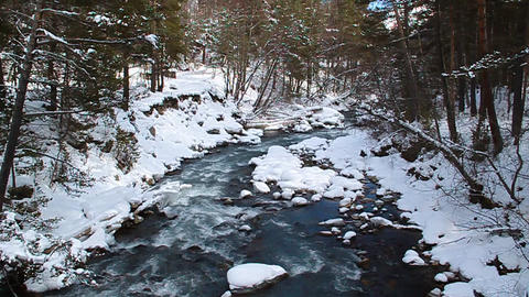 Pure blue mountain river flowing among the snow-co Footage