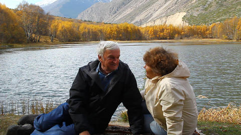 Happy Mature Man And Woman Sitting On The Shore Of stock footage