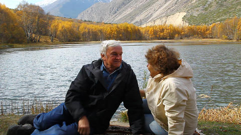 Happy mature man and woman sitting on the shore of Stock Video Footage