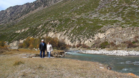 Happy elderly couple walking along the river bank, Stock Video Footage