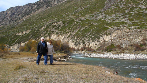 Happy elderly couple walking along the river bank, Footage