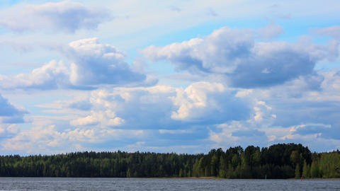 Fluffy Clouds Over The Forest Lake, Timelapse, 4K  stock footage