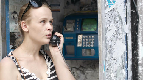 Attractive woman using a public telephone Stock Video Footage