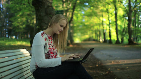 Young woman using her laptop in the park Stock Video Footage