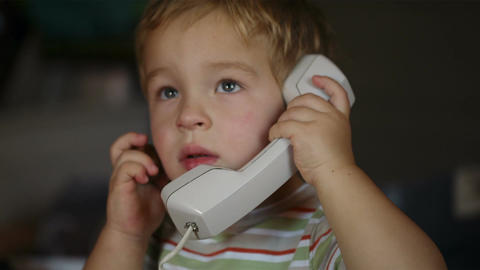 Excited little boy talking over telephone receiver Stock Video Footage