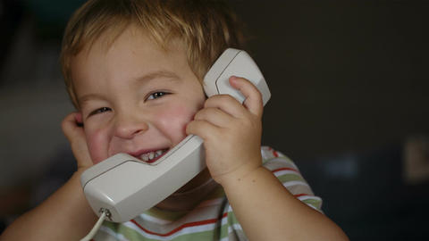 Excited little boy talking over telephone receiver Footage