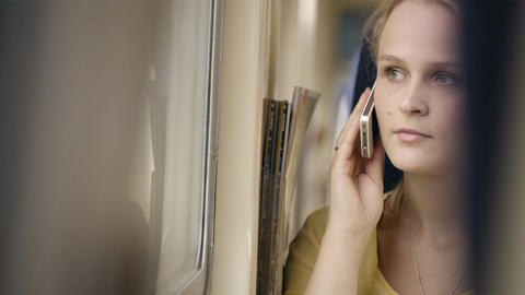 Woman talking on the phone in the train Stock Video Footage