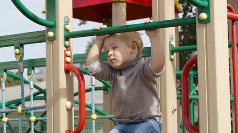 Boy on playground equipment Stock Video Footage
